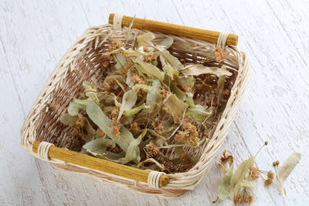 lime blossom: Dry linden flowers in the basket on wood background
