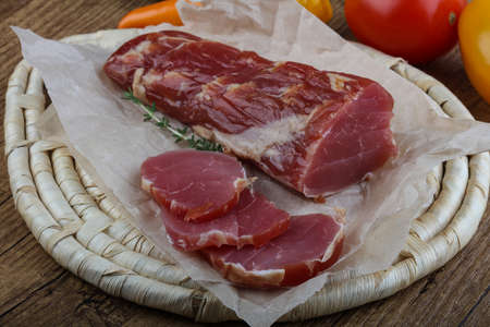 cured: Dry cured pork fillet on wood background