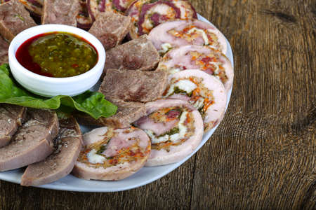 cutting horse: Horse sausages assortie with sauce and salad leaves Stock Photo