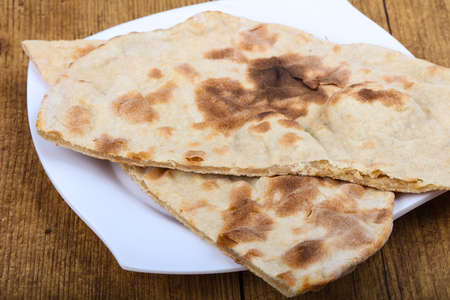 naan: Indian bread naan in the plate on wood background Stock Photo