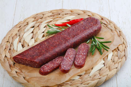 Dry salami with rosemary on the wood Stock Photo