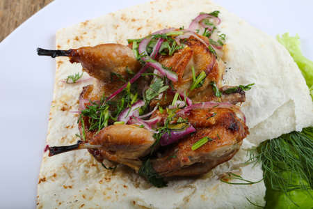 Grilled quail with onion and salad leaves