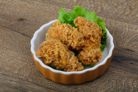 crispy: Crispy chicken wings with salad leaves on wood background