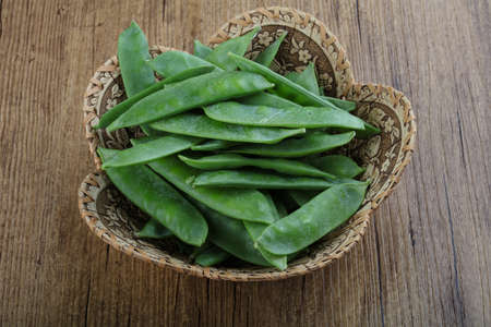 Green peas pods in the basket on wood