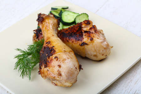 drumsticks: Roasted chicken legs with cucumber and dill leaves Stock Photo