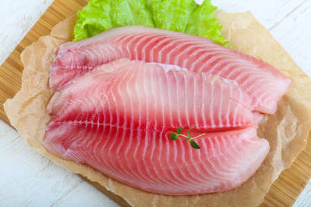 Raw tilapia fish fillet with thyme ready for cooking Stock Photo
