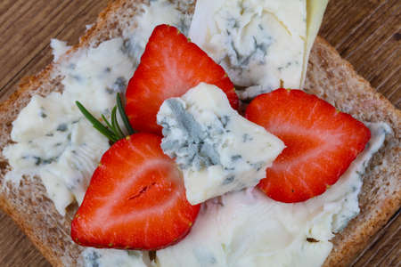 gorgonzola: Sandwich with gorgonzola and strawberry on the wood background Stock Photo