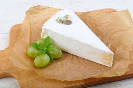 Brie cheese with grape on wood background Stock Photo