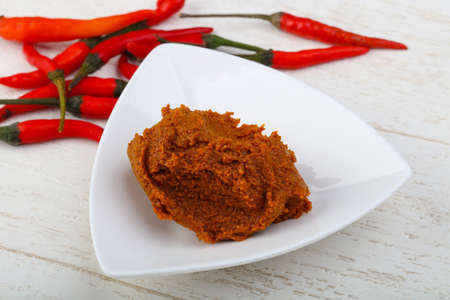 Spicy Chili paste with peppers on wood bacground