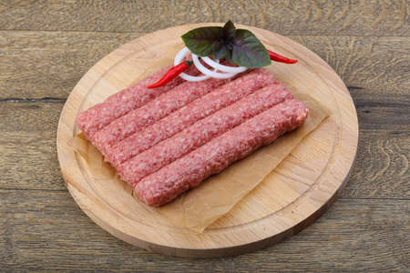 longaniza: Raw sausages for grill with onion and basil on wood background
