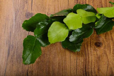 Kafir lime leaves on the wood background Stock Photo