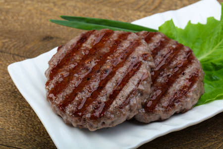 Grilled burger cutlet with onion and salad leaves