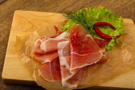 serrano: Ham serrano with salad leaves on wood background Stock Photo