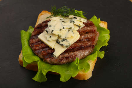 Sandwich with blue cheese and burger cutlet on black Stock Photo