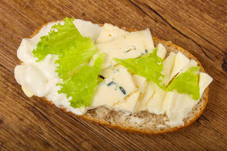 Three Cheeses sandwich with salad leaves on wood backgrond