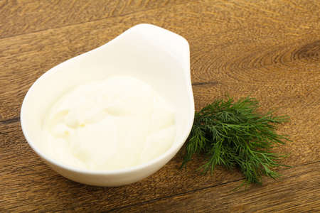 dill leaves: Greek yoghurt with dill leaves on wood background Stock Photo