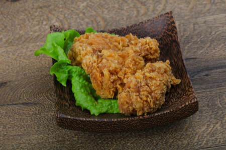 Crispy chicken wings with salad leaves on wood background