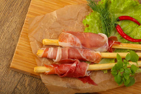Bread sticks with serrano and salad leaves