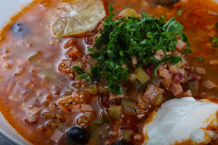 Solyanka mix soup with sausages, olives and lemon
