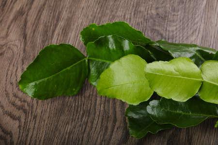 kafir lime: Kafir lime leaves on the wood background Stock Photo