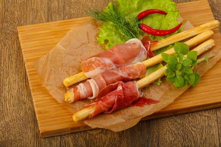 serrano: Bread sticks with serrano and salad leaves