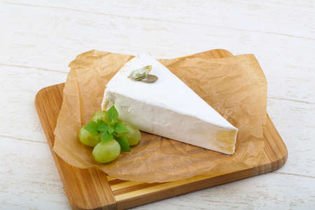 brie: Brie cheese with grape on wood background Stock Photo