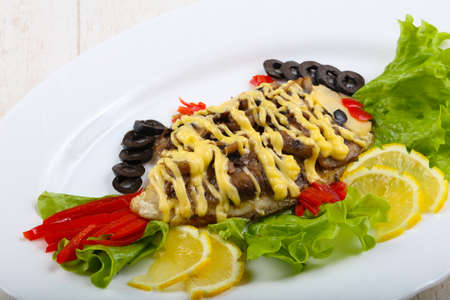 catfish: Tilapia fish fillet styled with salad, lemon and olives Stock Photo
