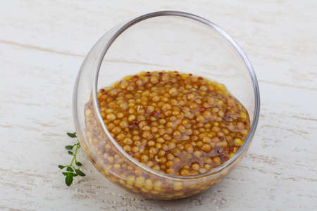 Mustard dijon in the bowl on wood bacground Stock Photo