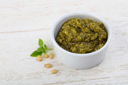 Pesto sauce in the bowl on wood background