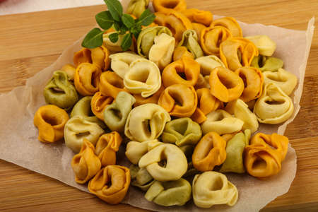 tortellini: Raw tortellini with basil - ready for cooking