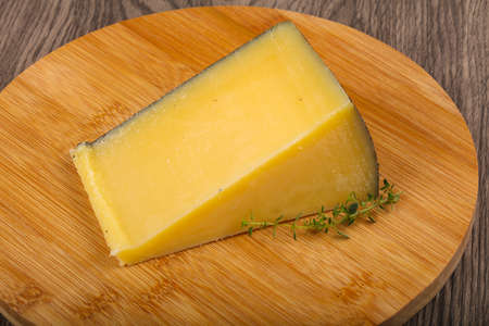 Parmesan cheese with thyme on the wood background