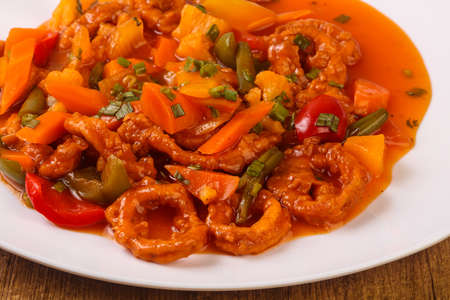 Squid rings in sweet and sour sauce with vegetables and spices