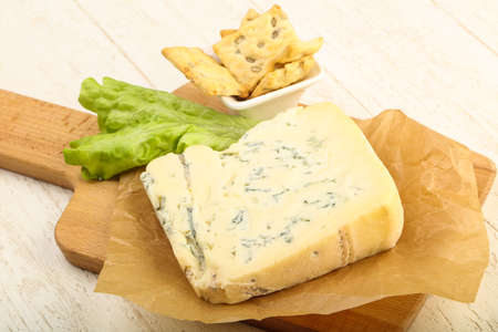 Gorgonzola cheese slice with salad leaves over the wooden background