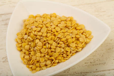 Yellow lentil ready for cooking over wooden background