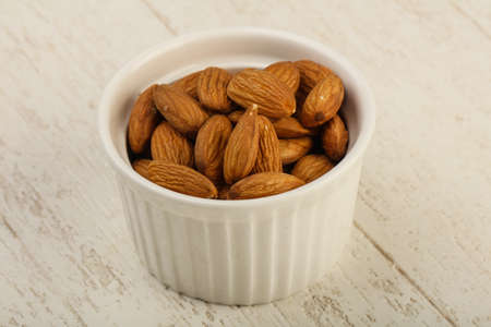 seed: Almond in the bowl over the wooden background