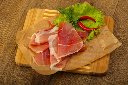 Ham serrano with salad leaves on wood background Stock Photo