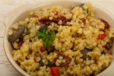 red quinoa: Bulgur with chicken hearts and dry tomatoes Stock Photo