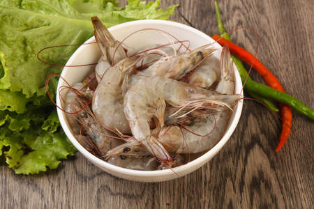 fish tail: Raw king prawn heap in the bowl over wooden background