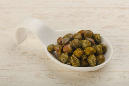 Marinated capers in the bowl over wood background