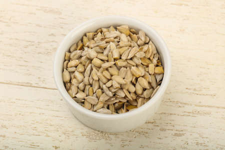 sunflower seeds: Peeled sunflower seeds heap over the wooden background Stock Photo