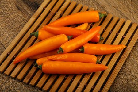 Hot yellow pepper heap over the wooden background Stock Photo