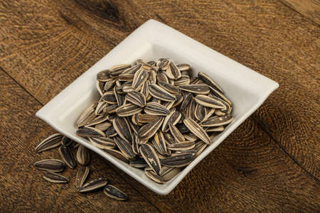sunflower seeds: Sunflower seeds in the bowl over the wooden background