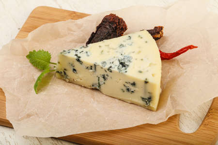 stilton: Blue cheese with mint over the wooden background