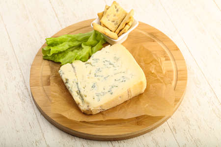 stilton: Gorgonzola cheese slice with salad leaves over the wooden background