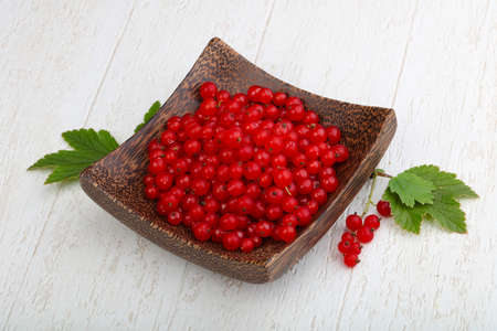 Red currants with leaves in the bowl on wood