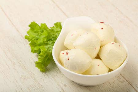 Midi Mozzarella balls in the bowl over wood background