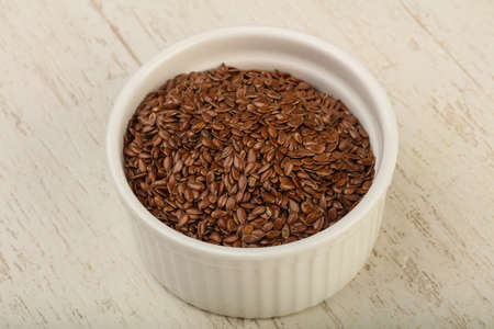 brown flax: Fry Flax seeds heap in the bowl over wooden background