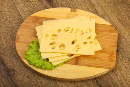 Sliced cheese with salad leaves over the wooden background