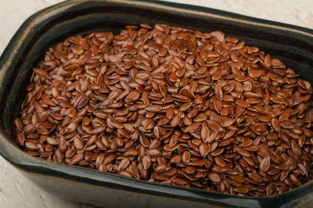 dietary fiber: Fry Flax seeds heap in the bowl over wooden background