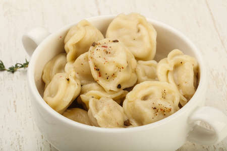 tortellini: Russian dumplings in the bowl with pepper and butter